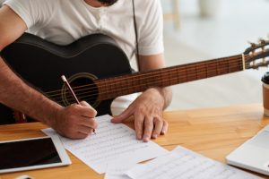 man songwriting with guitar